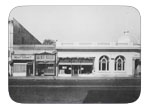 View of corner of North First and West B street circa 1946 Purity store, Dixon meat market, Beauty parlor, Gem pharmacy, and G.E.M. saloon, gardners appliance store and first national bank.
